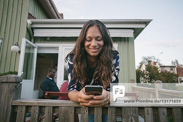 Lächelnde mittelgroße erwachsene Frau  die ein Mobiltelefon benutzt  während sie sich auf das Geländer der Veranda lehnt