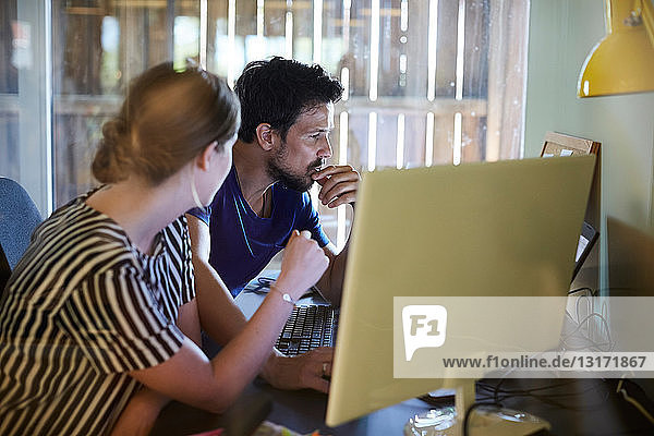 Male and female colleagues discussing at computer desk in creative office