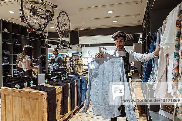 Salesman arranging clothes on rack while saleswoman assisting customers at store
