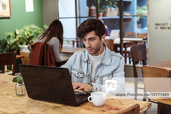 Young man using laptop while having coffee at table in cafe