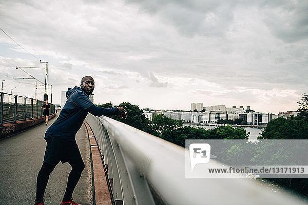 Portrait of tired sportsman leaning on railing at footbridge against sky