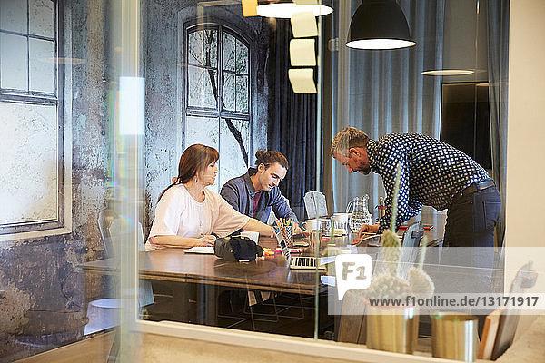 Kreative Geschäftsdiskussionen im Sitzungssaal durch Glas gesehen