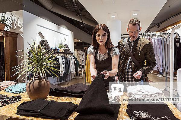 Verkäuferin zeigt Kunden Kleidung in einer Boutique