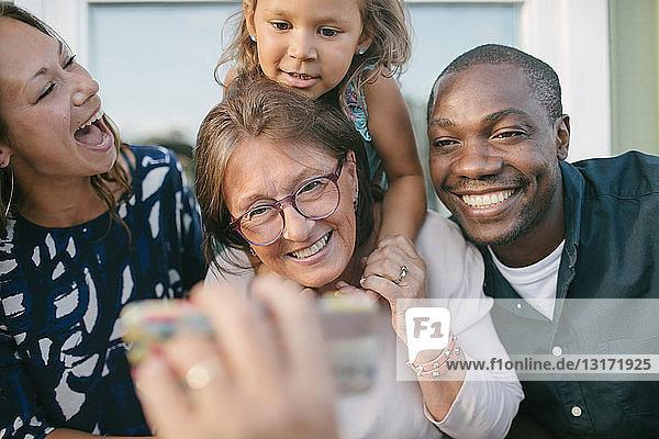 Ausgeschnittenes Bild eines Mannes  der seiner glücklichen Familie auf der Veranda ein Mobiltelefon zeigt