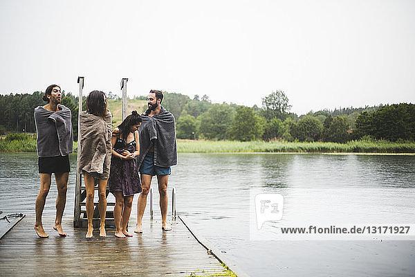 In Handtücher gewickelte Freunde unterhalten sich  während sie auf dem Steg über dem See vor klarem Himmel stehen