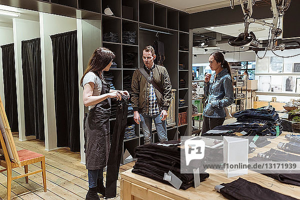 Saleswoman showing jeans to customers at store
