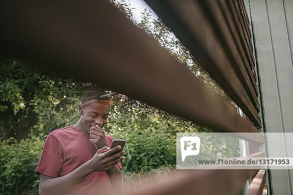 Lächelnder Junge mit Mobiltelefon durch den Zaun im Hinterhof gesehen