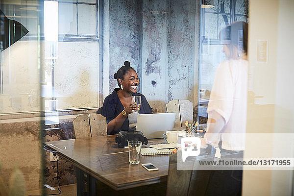Kreative Geschäftsfrau lächelt beim Glashalten während eines Treffens mit ihrem Amtskollegen