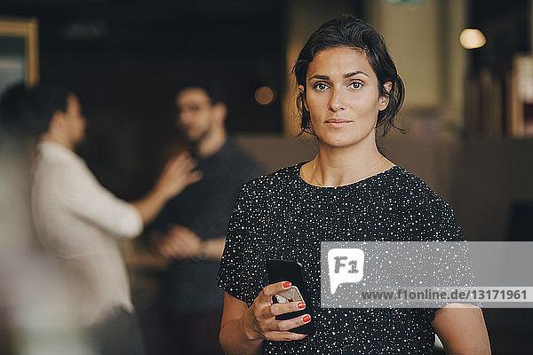Porträt einer selbstbewussten Geschäftsfrau  die im Kreativbüro ein Mobiltelefon in der Hand hält