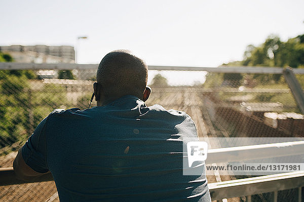 Rear view of exhausted male athlete leaning on railing during sunny day
