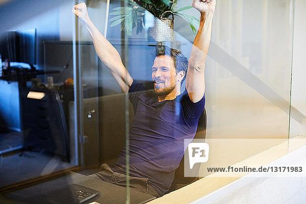 Kreativer Geschäftsmann sitzt mit erhobenen Armen durch Glas gesehen im Büro