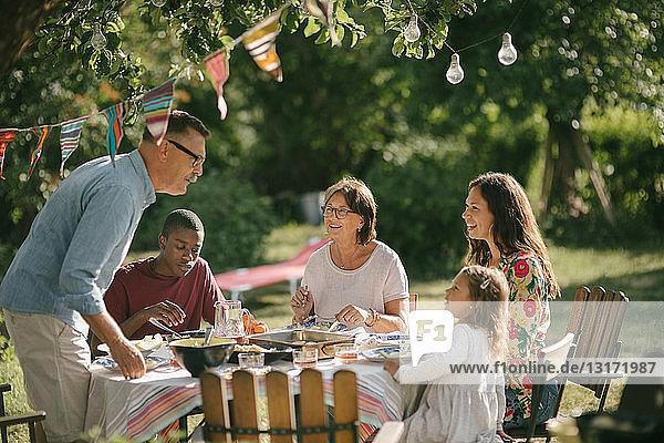 Älterer Mann und Enkelin unterhalten sich beim Mittagessen mit der Familie im Hinterhof während einer Party