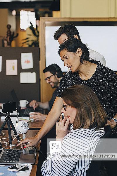 Mittlere erwachsene Geschäftsfrau diskutiert mit Team über Laptop im Büro