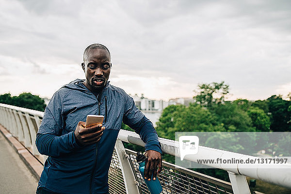 Sportsman using mobile phone while leaning on railing at footbridge against sky