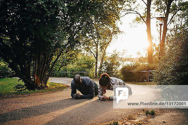 Male and female athletes doing planks on road in park during sunset