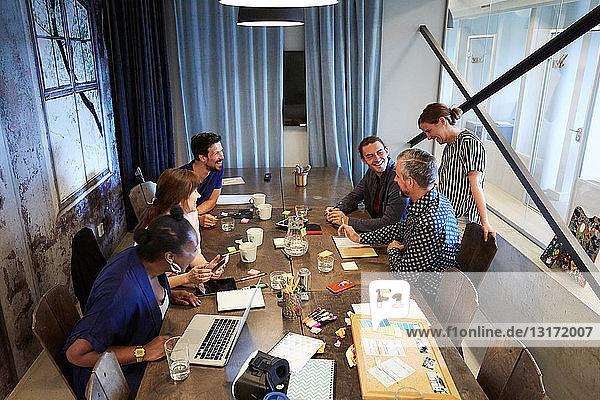 Schrägansicht von Kollegen  die während einer Besprechung im Büro am Konferenztisch diskutieren
