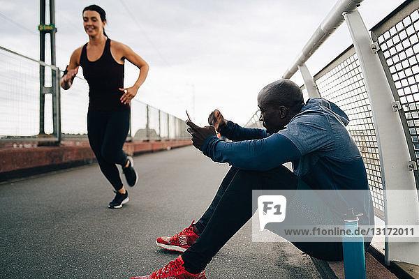 Sportler hält Handy in der Hand  während er die auf dem Steg laufende Sportlerin anfeuert