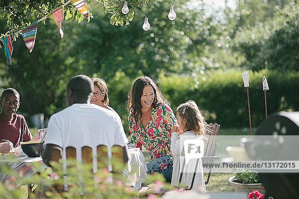 Glückliche Mehrgenerationen-Familie beim gemeinsamen Mittagessen auf der Terrasse während der Gartenparty