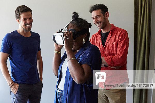 Geschäftsleute lächeln beim Anblick einer Kollegin  die einen Virtual-Reality-Simulator im Büro benutzt