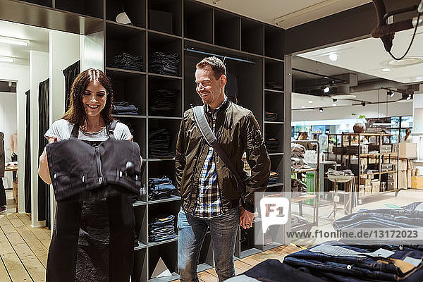 Smiling male customer looking at saleswoman holding jeans at store
