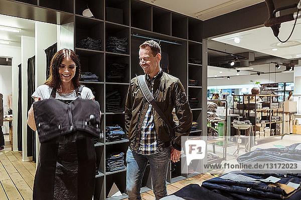 Lächelnder männlicher Kunde  der eine Verkäuferin mit Jeans im Laden ansieht