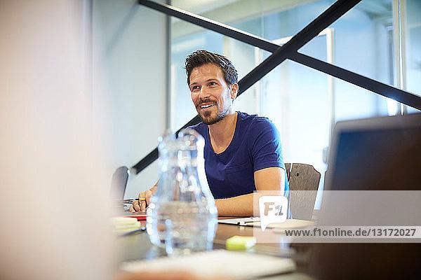 Kreativer Geschäftsmann schaut weg  während er am Konferenztisch im Sitzungssaal sitzt