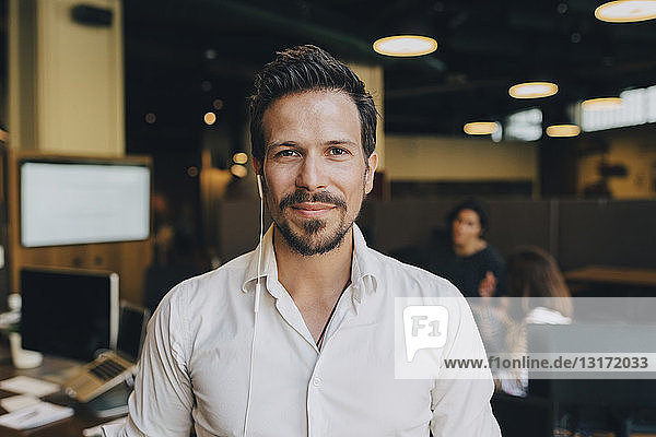 Porträt eines selbstbewussten Geschäftsmannes mit Kopfhörern im Amt