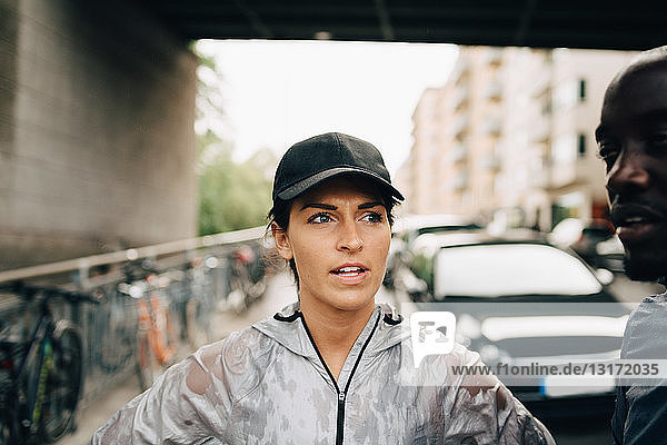 Female athlete talking with sportsman while standing on sidewalk in city