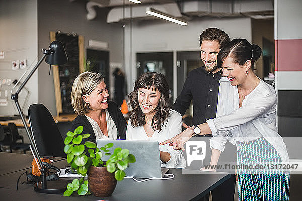 Creative business people smiling while discussing over laptop at desk in office