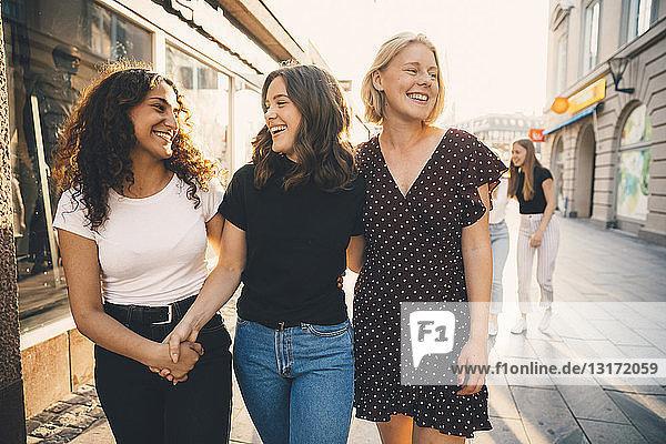 Lächelnde Freunde gehen bei Sonnenschein gemeinsam auf der Straße