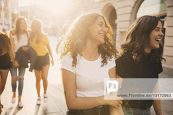 Glückliche Freunde  die bei sonnigem Wetter auf der Straße gehen  während sie in der Stadt unterwegs sind