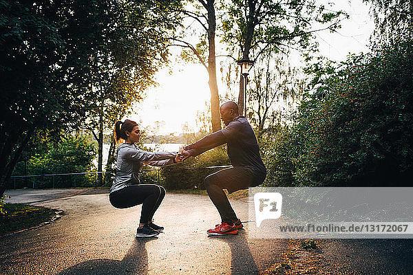 Männliche und weibliche Athleten halten sich beim Üben der Stuhlposition auf der Straße im Park an den Händen