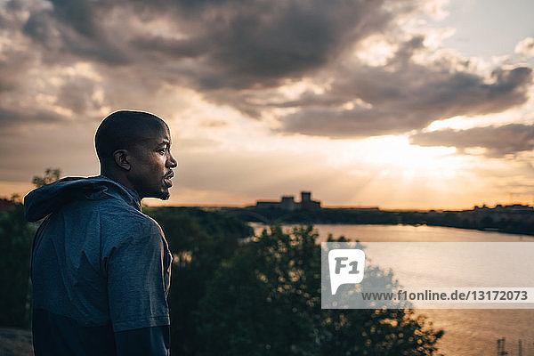 Male athlete looking away while standing on hill against sky during sunset