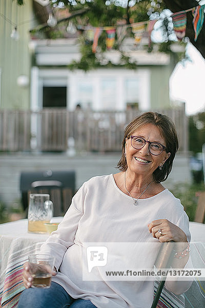 Porträt einer lächelnden älteren Frau  die ein Getränk in der Hand hält  während sie auf einem Stuhl am Tisch im Hinterhof sitzt