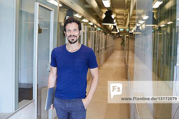Porträt eines selbstbewussten Geschäftsmannes  der einen Laptop in der Hand hält  während er im Korridor eines kreativen Büros steht