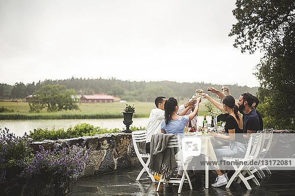 Männliche und weibliche Freunde stoßen am Esstisch auf Getränke an  während sie das Wochenende im Hinterhof verbringen