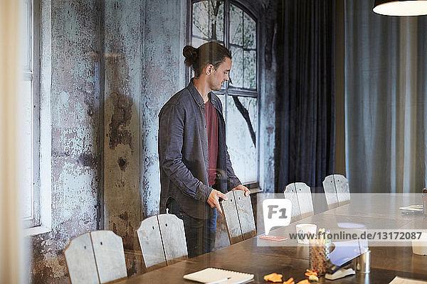 Junger kreativer Geschäftsmann arrangiert Stuhl im Sitzungssaal
