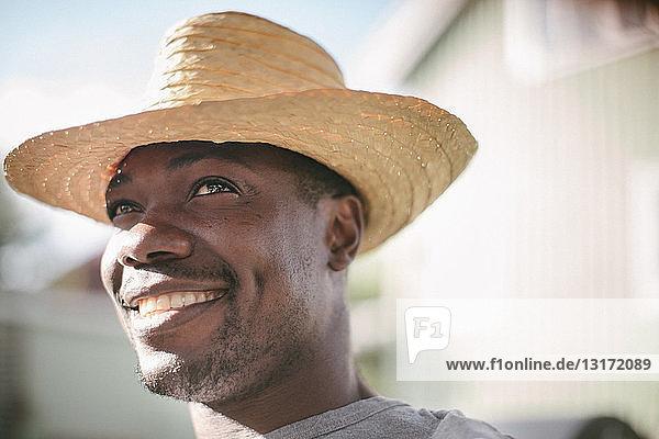 Lächelnder mittelgroßer Mann schaut weg  während er während der Gartenparty einen Strohhut trägt