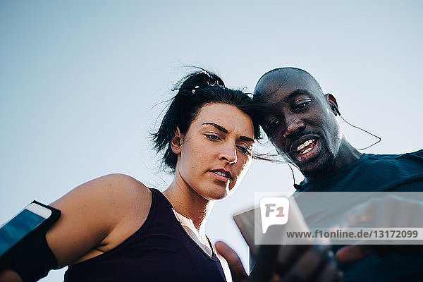 Low angle view of sportsman showing mobile phone to female athlete while standing outdoors