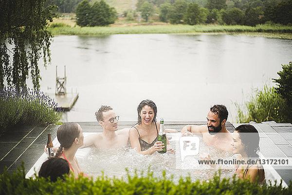 Cheerful male and female friends enjoying drinks in hot tub against lake during weekend getaway