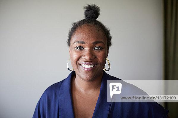 Porträt einer selbstbewussten kreativen Geschäftsfrau  die im Büro an einer grauen Wand steht