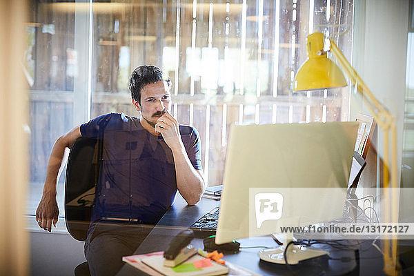 Kreativer Geschäftsmann schaut im Büro auf den Computermonitor