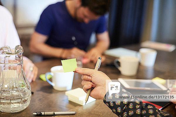 Abgetrennte Hand eines Geschäftsmannes  der während eines Treffens im Kreativbüro eine Haftnotiz hält