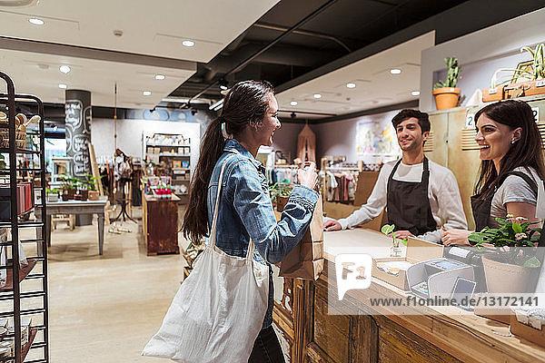 Seitenansicht eines Kunden  der im Geschäft mit männlichen und weiblichen Besitzern spricht