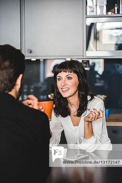 Geschäftsfrau lächelt beim Gespräch mit einem männlichen Kollegen am Tisch im Büro