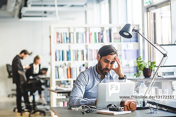 Tensed male entrepreneur looking at laptop while sitting in office