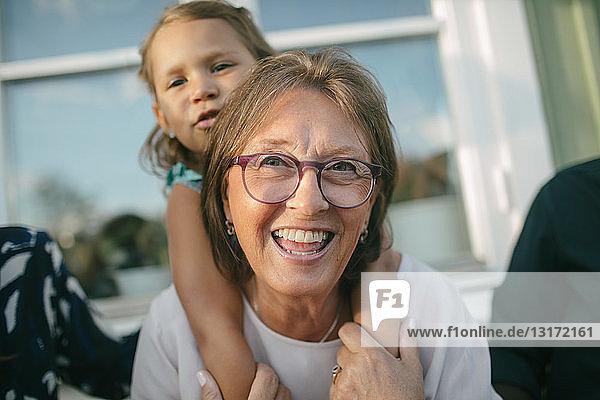 Glückliche ältere Frau  die ihre Enkelin auf der Veranda huckepack nimmt