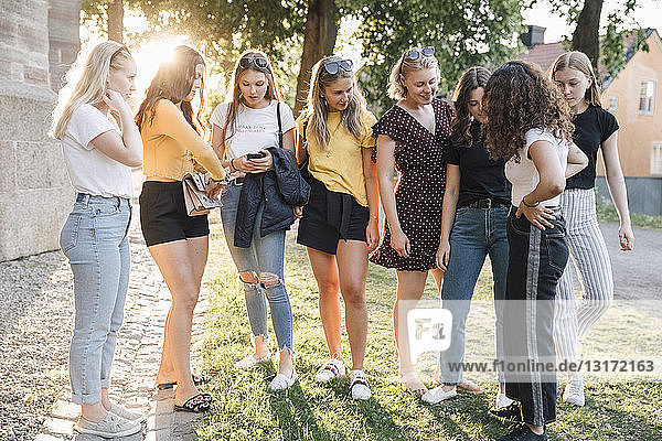 Full length of female friends standing on grass at park during sunny day