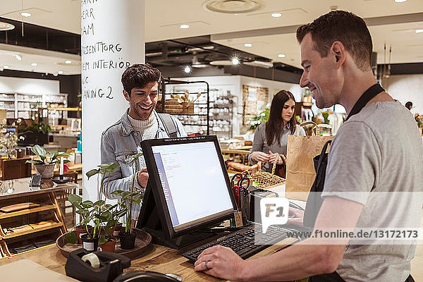 Cashier using computer while talking to smiling customer at checkout counter