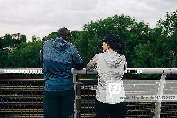 Rear view of male and female athletes talking while leaning on railing on footbridge